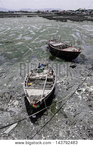 two fishing boat lie down on mud when the neap tide