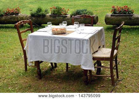 Wooden tablecloth set with a formal table setting and two chairs for al fresco dining on a private lawn in summer sunshine