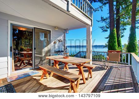 Walkout Deck  With Wooden Table Set And Amazing Water View.