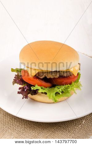 home made hungarian burger with salad sliced cheese and tomato slices on a plate