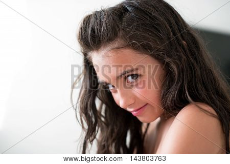 Clever attractive young girl with log brown hair looking sideways at the camera with a coy smile over white with copy space