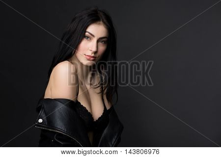 Picture of beautiful brunnette model woman in black lingerie or underwear showing her perfect body while posing for photographer in studio.
