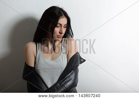 Picture of beautiful brunnette model woman looking down while posing isolated on white background in studio. Studio shot. Fashion or vogue concept.