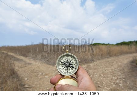 Man holding a compass on a fork in the road on a decision dilemma direction concept