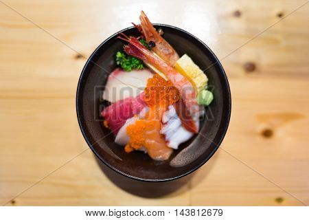 Chirashi sushi Japanese food rice bowl with raw salmon sashimi tuna and other mixed seafood top view center aligned with copy space on wooden table focus on salmon eggs with depth of field effect