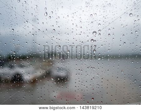 Water drop on mirror window of airplane in rainy day while landing at airport with blur car outside. Safety in transportation and travel concept.