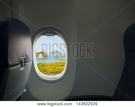 Island sea and mountain view from window of airplane. Travel vacation and journey concept.