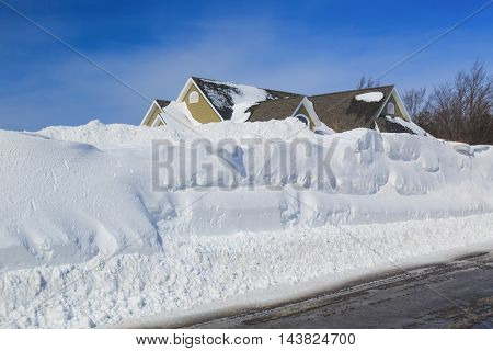 High snowbanks on the sides of a plowed road in an urban neighborhood.