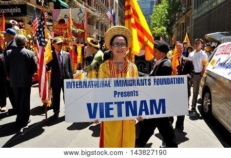 New York City - June 22 2013: Vietnamese woman dressed in traditional Ao Dai clothing from her country holds the presentation sign for the Vietnam contingent of marchers at the International Immigrants Foundation Parade