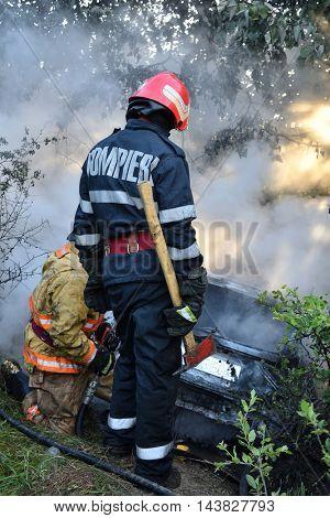 TULCEA, ROMANIA - JUNE 11: Danube Delta Rally special trial windfarm on June 11, 2016 in Tulcea, Romania; car on fire and firemen trying to estinguish fire