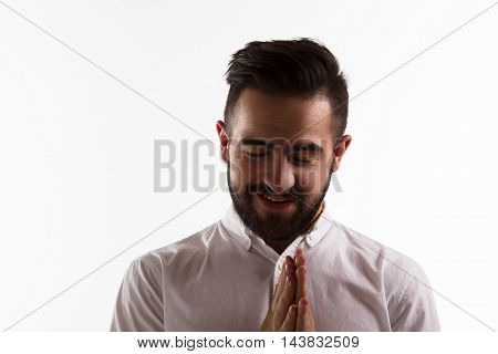 Portrait of handsome man smiling with his eyes closed isolated on white background. Barded hipster man happy laughing in studio. Hard light concept.