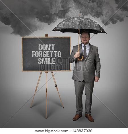 Dont forget to smile text on blackboard with businessman holding umbrella