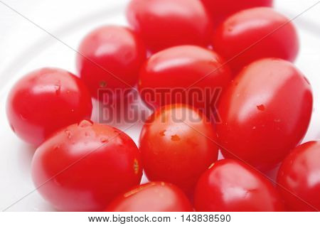 HOMEGROWN PLUM TOMATOES IN VIVID RED.  Plate of fresh, homegrown and healthy tomatoes on a white background. Delicious, organic, natural food ready to eat.