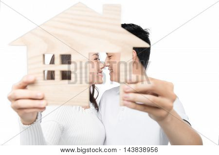 real estate family and couple concept - smiling couple hugging with symbol house and key daydreaming at home