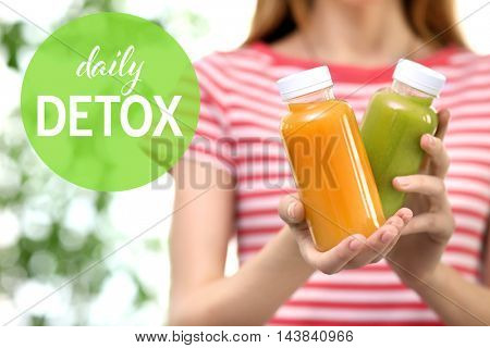 Woman holding bottles with delicious detox drinks. Text daily detox on blurred background. Detox diet concept.