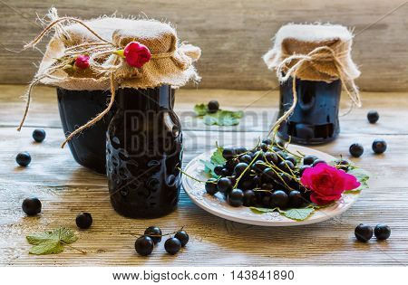 Preserved homemade black currant jam in glass jars on light wooden table. Fresh berries and green leaves white vintage plate.