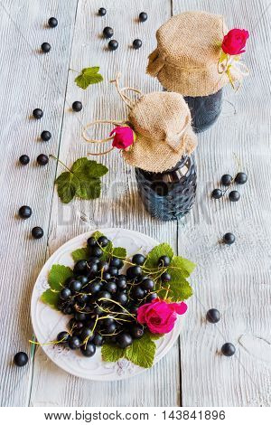 Preserved homemade black currant jam in glass jars on wooden table. Fresh berries and green leaves vintage white plate top view.