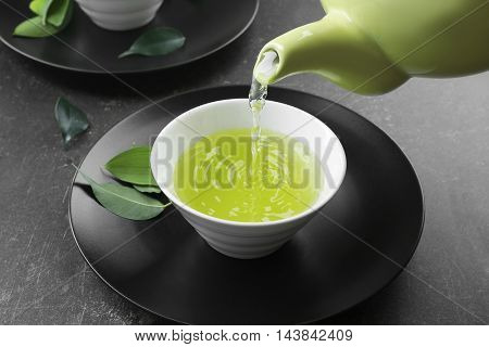 Pouring fresh matcha tea in cup on grey background