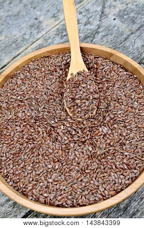Flaxseed in a bamboo bowl on rustic wooden table