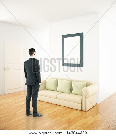Businessman looking at blank picture frame in interior with couch. Mock up 3D Rendering