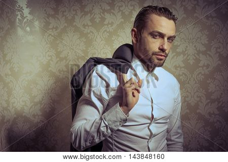 Young handsome man holding a jacket posing isolated over vintage background