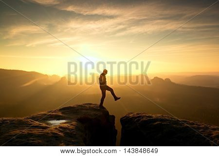 Crazy hiker umping between rocks. Marvelous colorful daybreak in rocky mountains heavy orange mist in deep valley. Miracle of nature poster