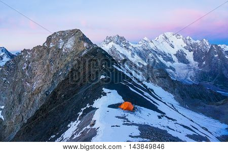 Lonely mountaineers camp on the pass Koyavganaush in very high snowy mountains. Picture was taken during a trekking hike in the amazing Caucasus mountains Adyl-su region Kabardino-Balkaria Russia