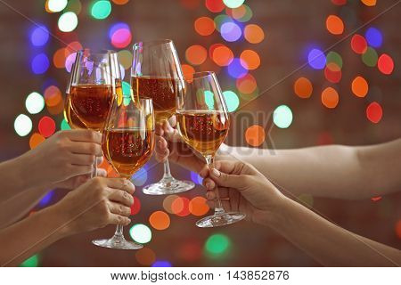 Female hands clinking glases with white wine on bokeh background