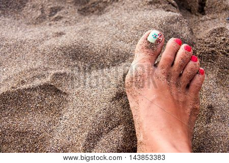 Women's feet with a pedicure in the sand on the beach.