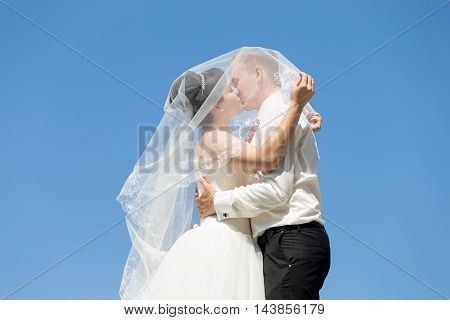 Portrait Of Kissing Newlyweds