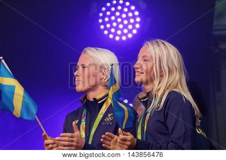 STOCKHOLM SWEDEN - AUG 21 2016: Happy swedish female wrestler Jenny Fransson and Sofia Mattson waiving a flag when swedish olympic athletes are celebrated in Kungstradgarden StockholmSwedenAugust 212016