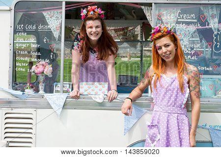 Two Smiling Ladies Wearing Vintage Dresses With Ice Cream Van