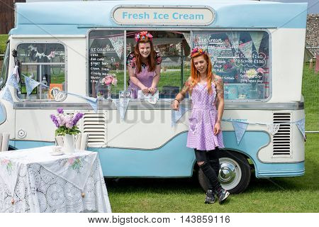 Two Young Ladies Wearing Vintage Dresses With Ice Cream Truck