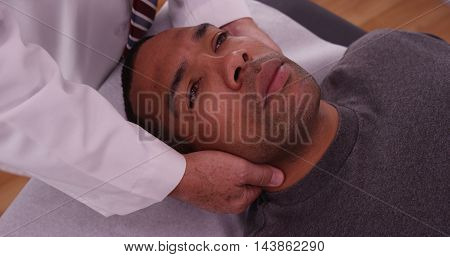 Chiropractor Checking Neck Injury Of African Male Patient