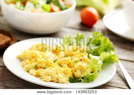 Scrambled eggs with vegetables on a grey wooden table