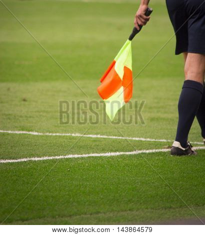 Soccer Referee with orange and yellow flag