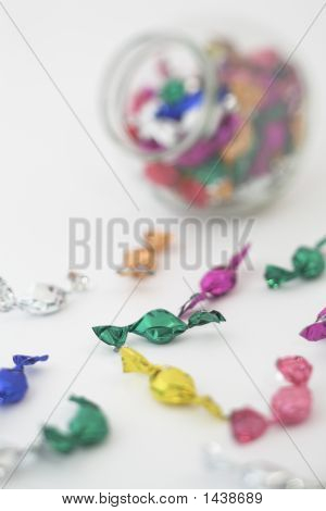 Candies wrapped in colorfull paper in front of a candy jar. Shallow DOF on a green candy. The jar is out of focus. poster