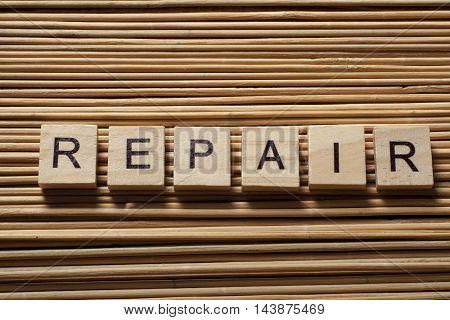 text of REPAIR on wood abc cubes at wooden background.