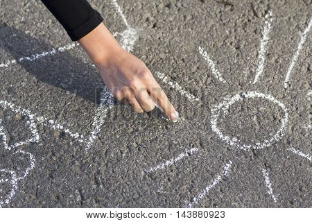 Hand girl draws by a chalk picture House and the Sun on asphalt in the summer outdoors