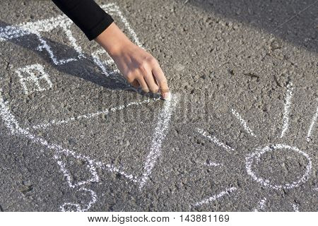 Hand girl draws by a chalk picture House and the Sun on asphalt