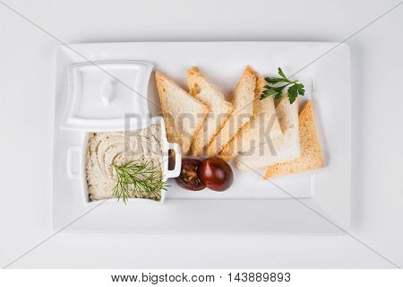 Forshmak with toast, tomatoes anf sauce on white plate