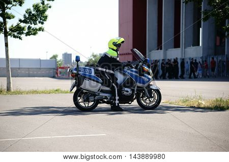 MAINZ, GERMANY - AUGUST 06: A policeman on a motorcycle watches fans at the entrance of the Opel Arena at a soccer game of 1. FSV Mainz 05 on August 06, 2016 in Mainz.