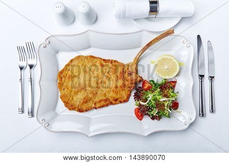 Veal Milanese recipe from the restaurant with lettuce tomato lemon and fried pork cutlet