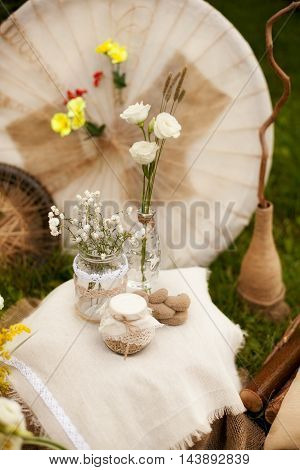wedding decorations for a photo shoot in the style of shabby chic vintage jars with flowers are on linen fabric on the background of wheels decoupage