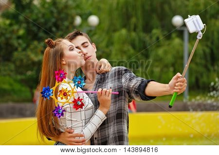 Enamoured teenagers do selfie. Girlfriend and boyfriend strolling in a city park. Boy holding a selfie stick with a smartphone and hugs girl. Girl holds a the spinner and kisses her boyfriend. First love. He falls in love. Date.