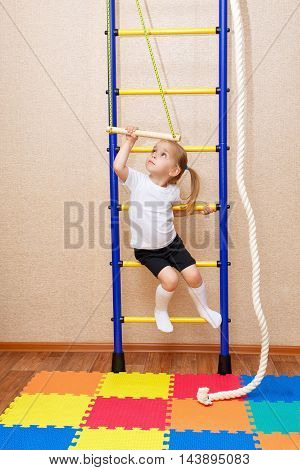 Little girl hanging on the crossbar. Wall bars. Sports Equipment. Children's sports.