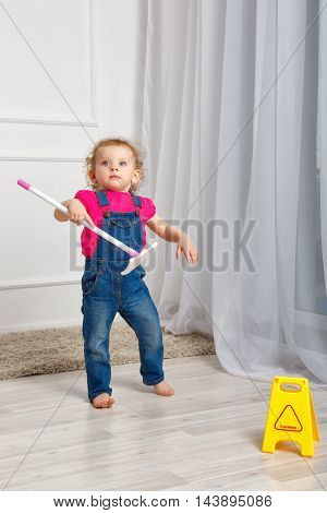 Little girl is cleaned with a mop in his hands. Small mother's helper. Household chores.