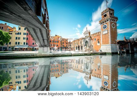 View on venetian Arsenal with reflection on the water in Castello region in Venice. Long exposure image technic with motion blurred clouds and glossy water