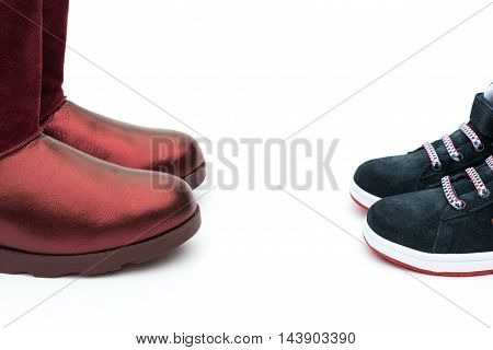 black shoes for son and red ones for mom on white as filiation concept