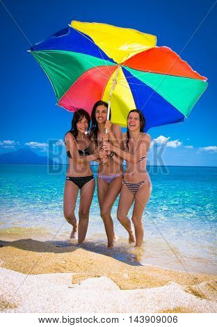 Three beautiful attractive young women with umbrella walking on the beach